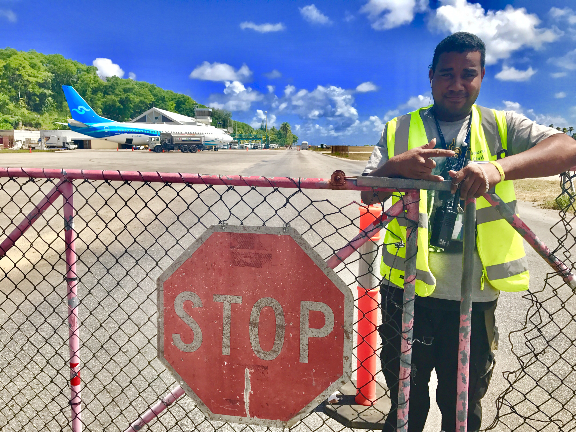 Nauru ramblin randy airport security minds the gate blocking traffic while a plane crosses the street nauru097 sciox Image collections